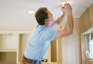 Senior Living maintenance manager fixing light bulb